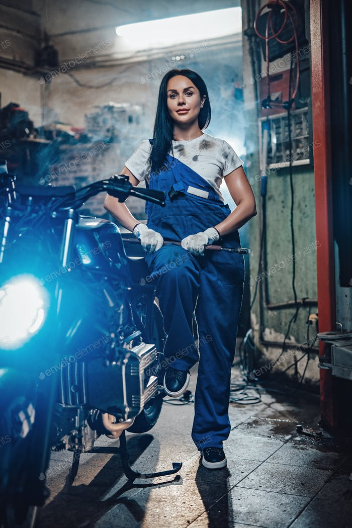 Beautiful brunette woman in blue overalls posing next to a custom bobber in garage or workshop