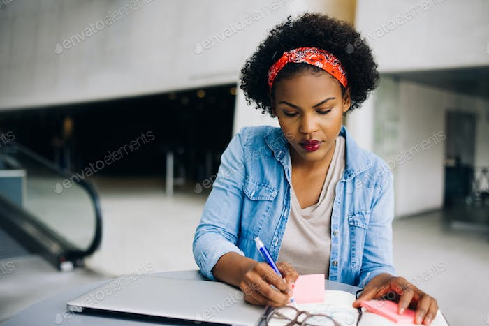 Focused young African female entrepreneur working in an office lobby