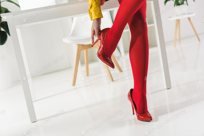 cropped view of stylish woman in red tights and heels