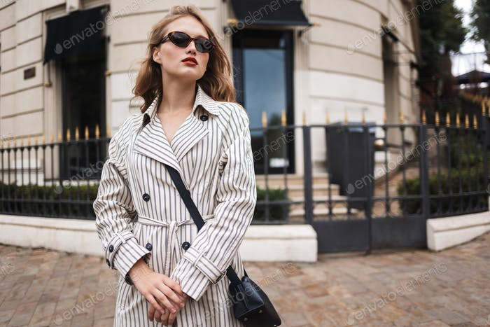 Beautiful girl in striped trench coat with little black cross ba