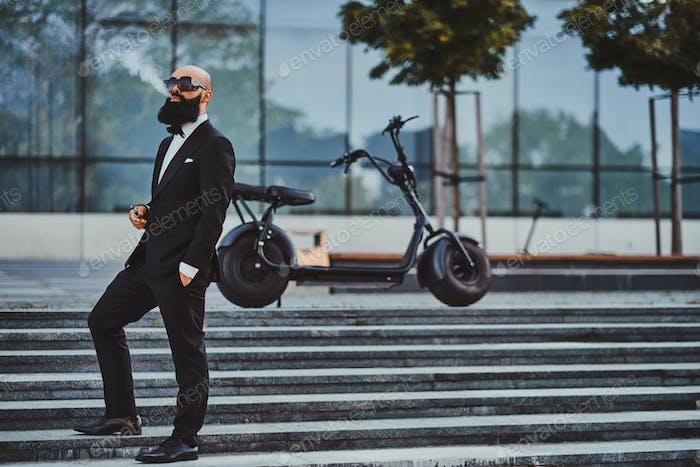 Человек позирует рядом со своим современным электро велосипедом