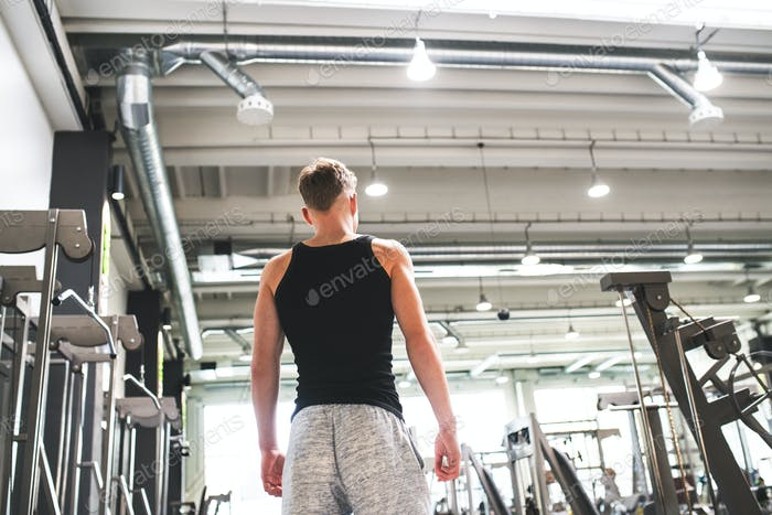 Young man in modern crossfit gym, standing. Rear view.