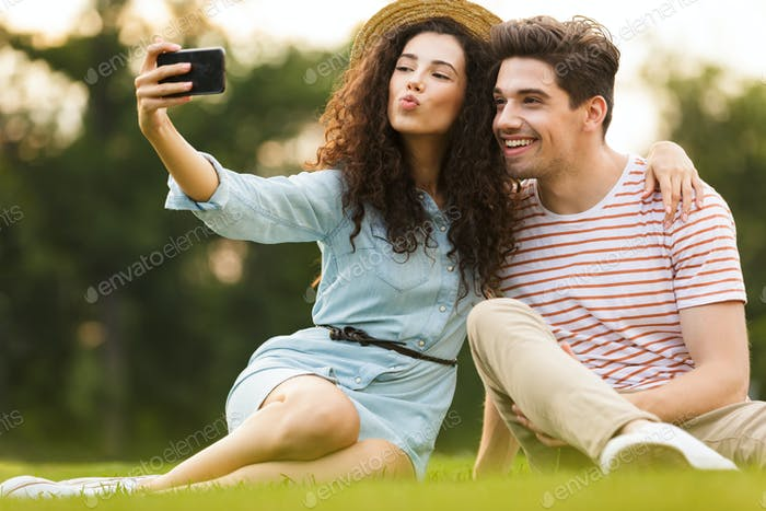 Image of lovely couple man and woman 20s sitting on green grass
