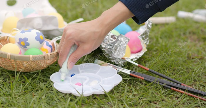 Painting on egg for Easter holiday at outdoor green park