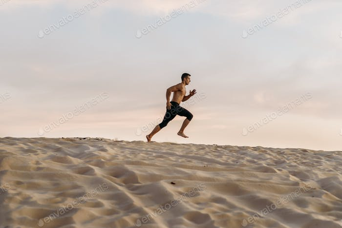 Athlete on running workout in desert at sunny day