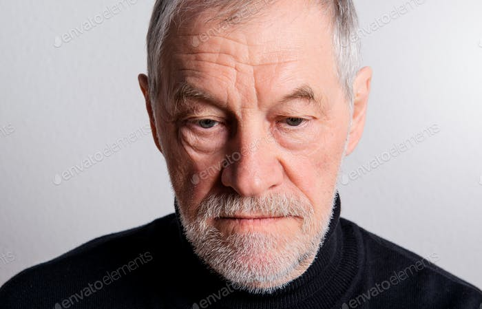 Portrait of a sad senior man with beard and mustache in a studio.