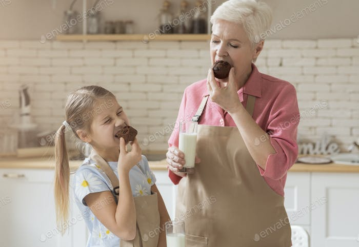 Grandma and granddaughter eating tasty chocolate muffins in kitchen