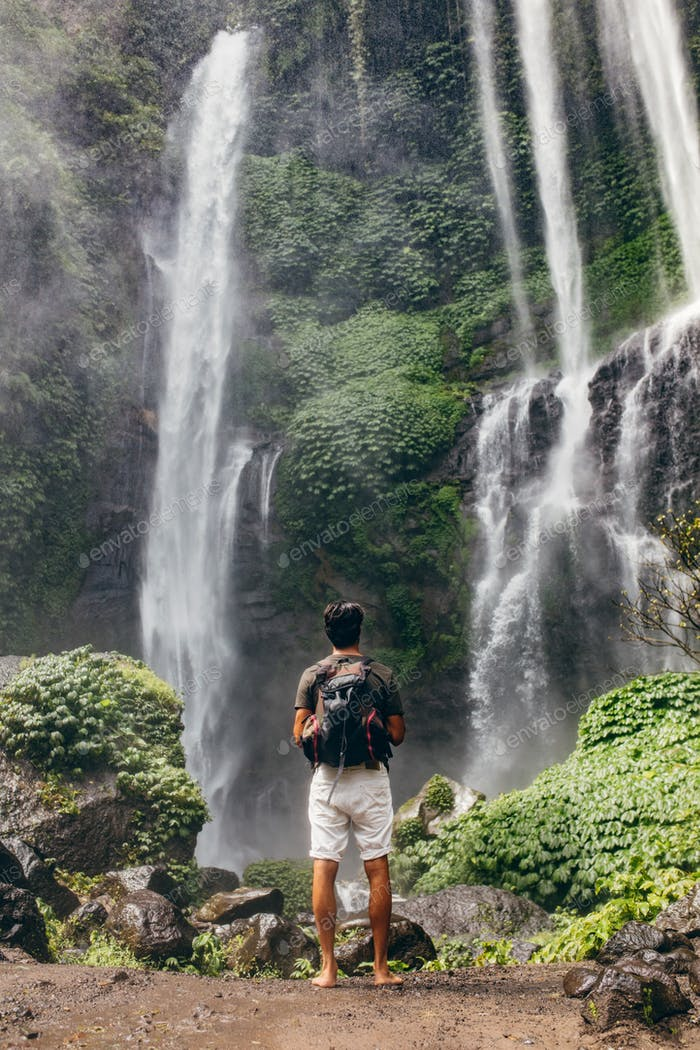 Young male hiker looking at waterfall