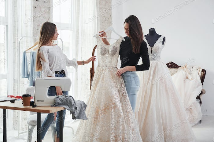 Dress in full height. Two female fashion designers works on the new clothes in the workshop