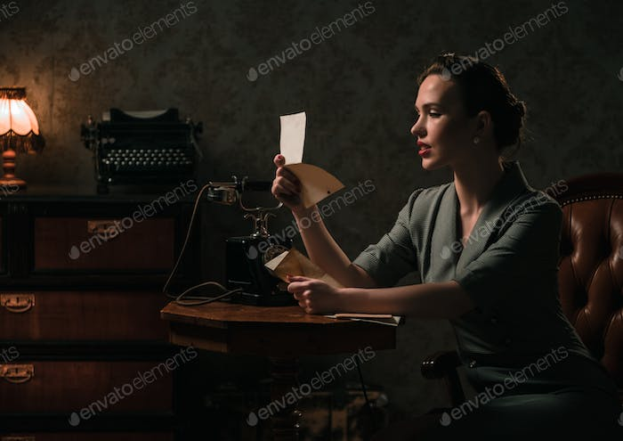 Beautiful woman reading letter in retro interior
