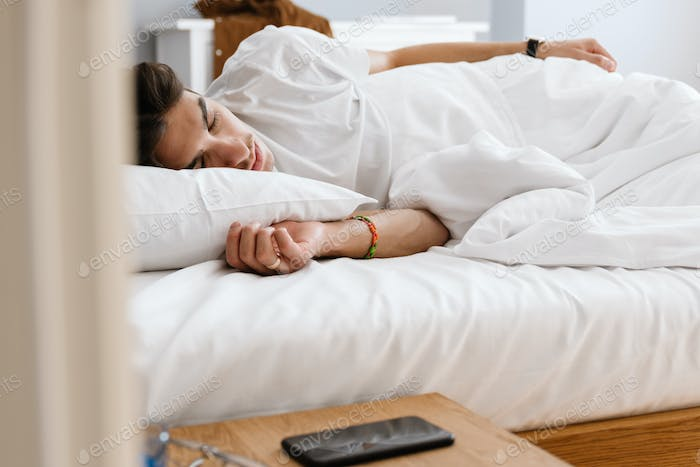 Man sleeping in bed indoors at home