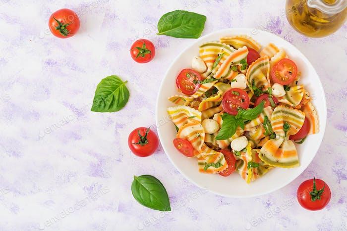Pasta de color ensalada farfalle con tomates, mozzarella y albahaca.