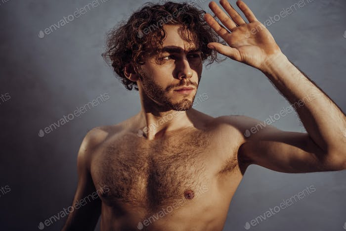 Naked and attractive man with curly hair posing for a photoshoot on a grey background