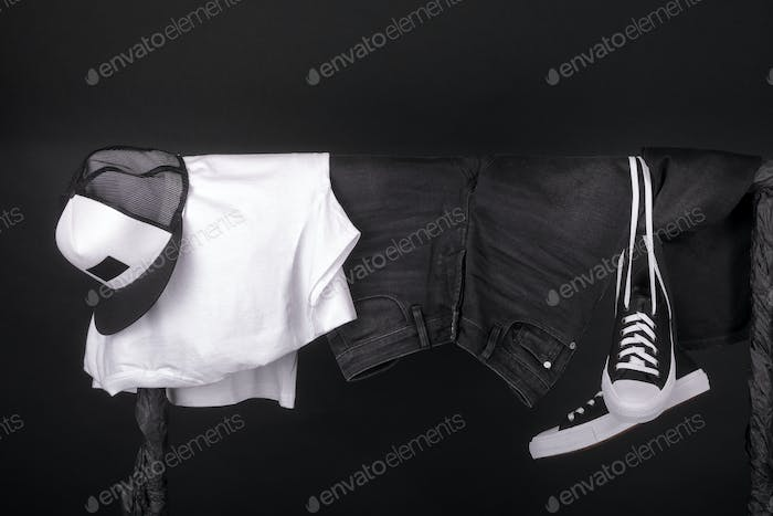 Hanging clothing. Black and white sneakers, cap  jeans on clothes rack   background. Copy space.