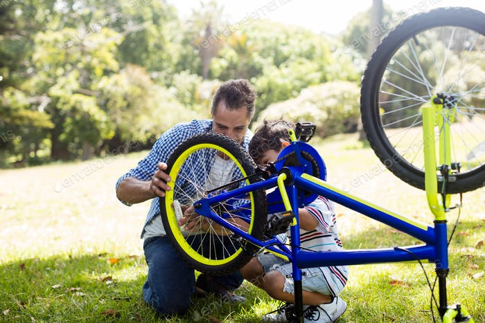 Son and father repairing their bicycle in park