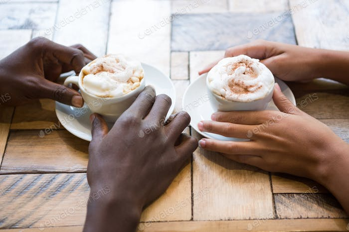 Multi ethnic couple hands holding coffee cups in cafe