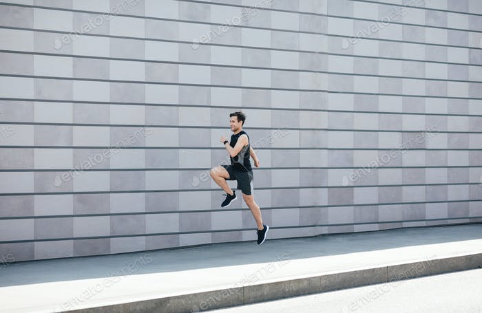 Jogging with jumping. Guy runs at path near gray brick wall in city