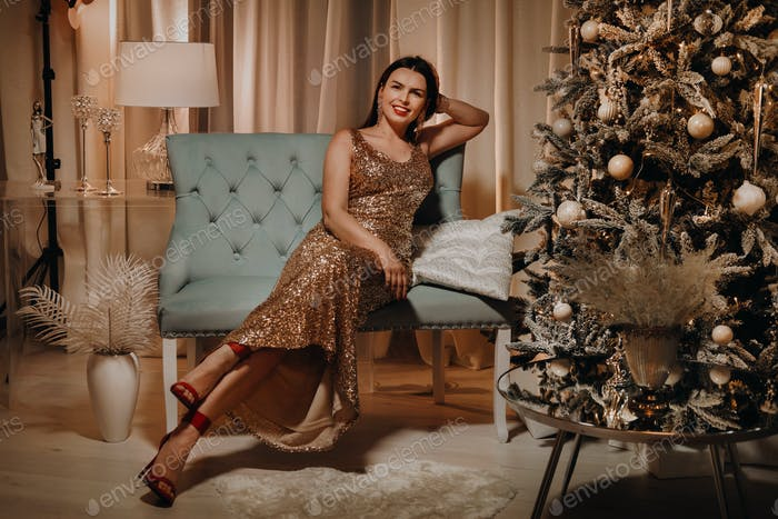 A girl in an evening dress is sitting on the sofa near the Christmas tree