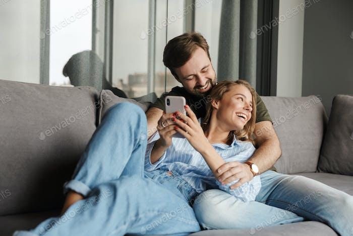 Foto von lustigen schönen schönen Paar lachen und mit Handy