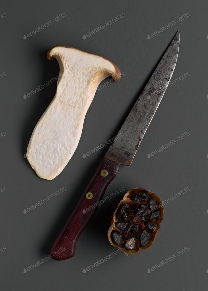 black garlic mushrooms and old knife on gray board, top view