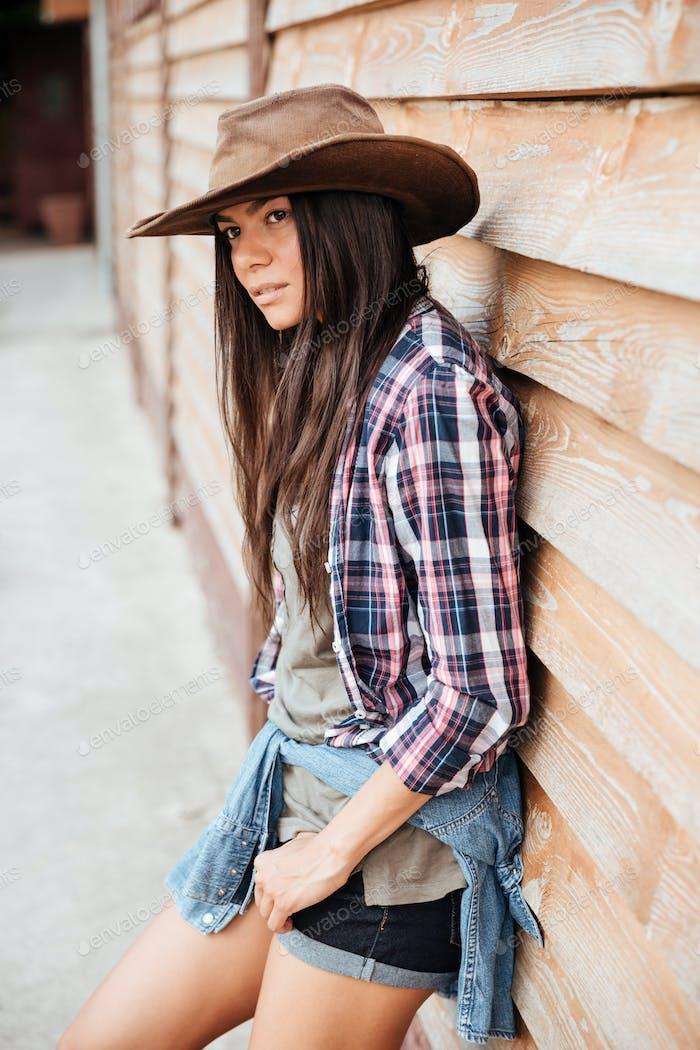 Schöne junge Frau Cowgirl in Hut und kariertes Hemd