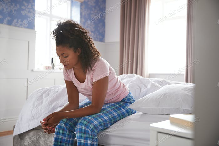 Woman Wearing Pajamas Suffering With Depression Sitting On Bed At Home