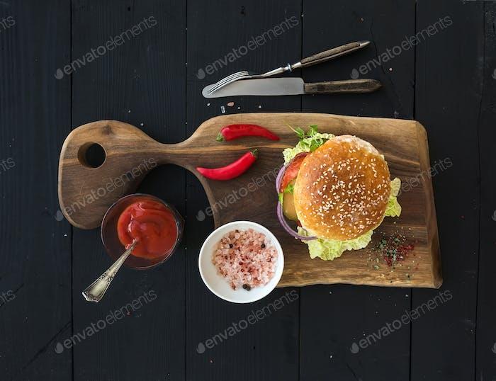 Fresh homemade burger on dark serving board with spicy tomato sauce, sea salt