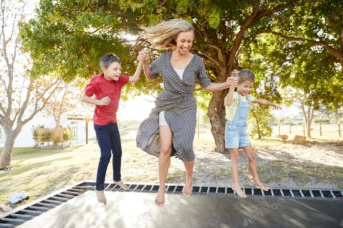 Mother Playing With Children On Outdoor Trampoline In Garden