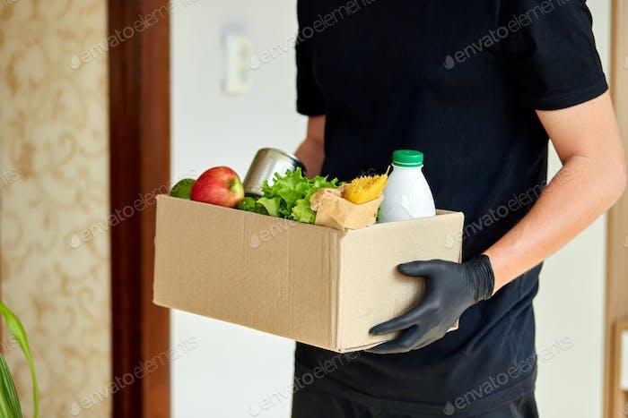Freiwillige in der medizinischen Schutzmaske und Handschuhe Lieferung Spendenbox zu Hause