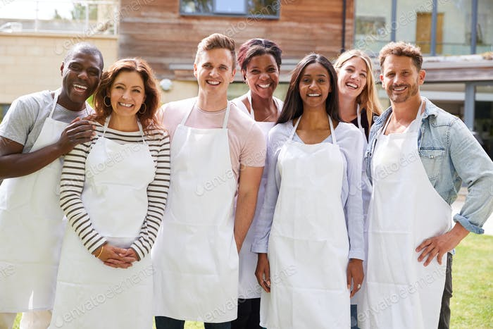 Group Portrait Of Men And Women Attending Cookery Class Relaxing Outdoors