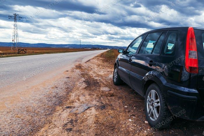 Gebrochenes Auto hat an der Straße am stürmischen Tag angehalten