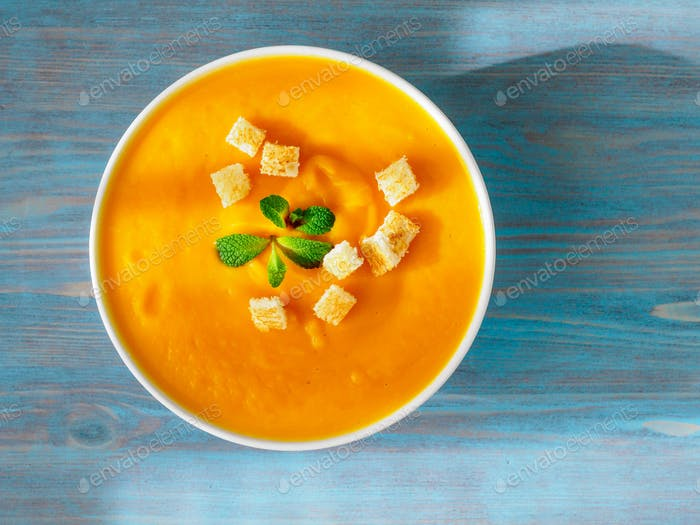 große Schüssel Kürbissuppe auf einem hölzernen blauen Hintergrund. Helles schmackhaftes Gericht, Draufsicht