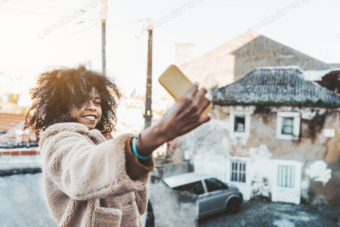 Curly-hair girl is taking a selfie