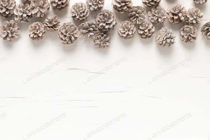 Christmas, New Year or Noel holiday festive winter greeting card with pine cones on white background
