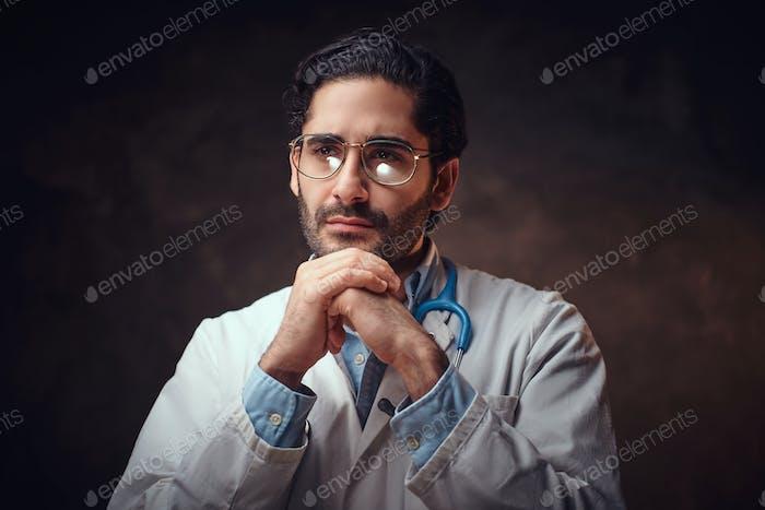 Portrait of smart handsome doctor over dark background.
