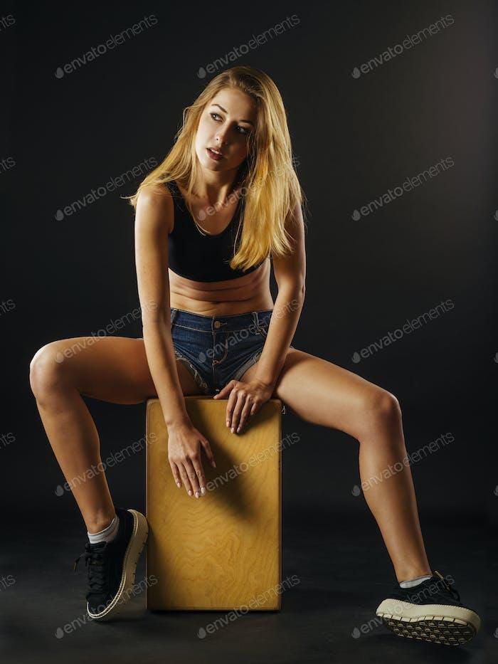 Schöne junge Frau spielen die Cajon