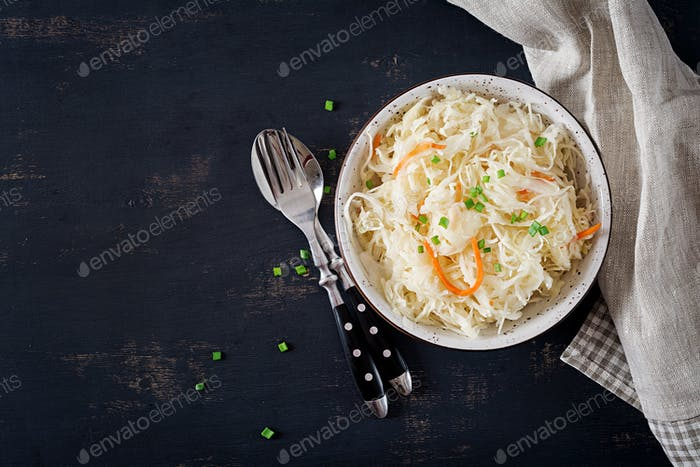 Fermented cabbage. Vegan food. Sauerkraut with carrot and spices in bowl on the dark background.