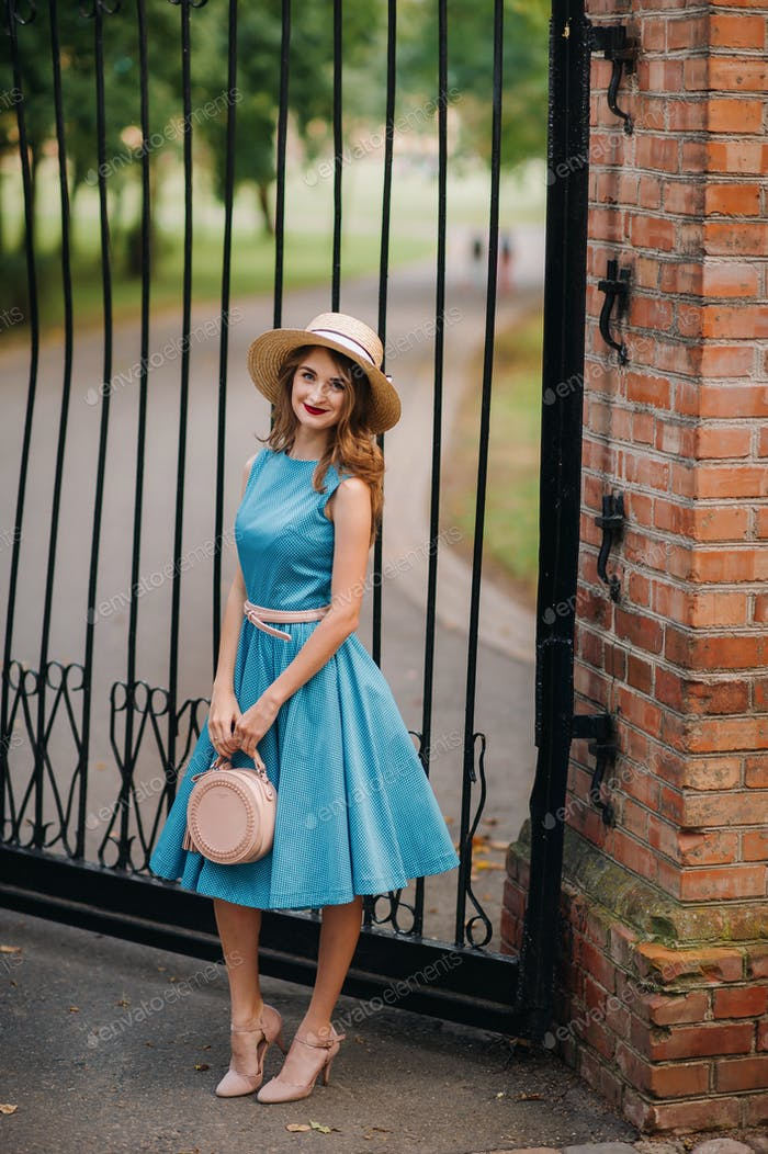 Fashionable girl in a blue dress and elegant hat on the street