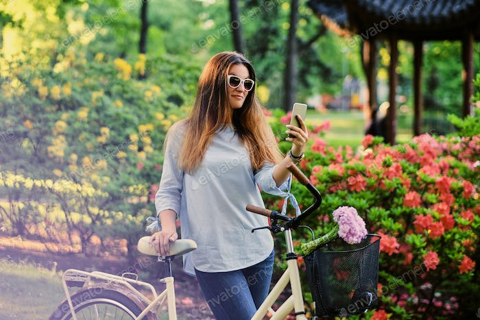A woman with city bicycle in a summer outdoor park.