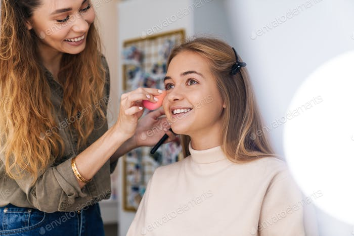 Beauitufl smiling young woman getting her makeup done