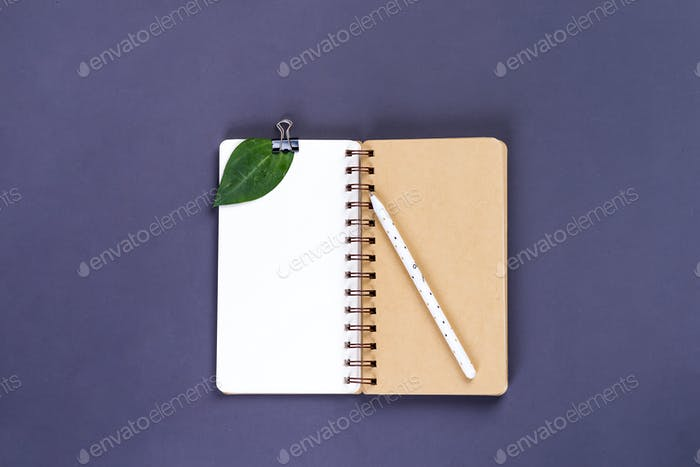 Mockup blank paper notebook and green leaf on a gray background. Flat lay, top view