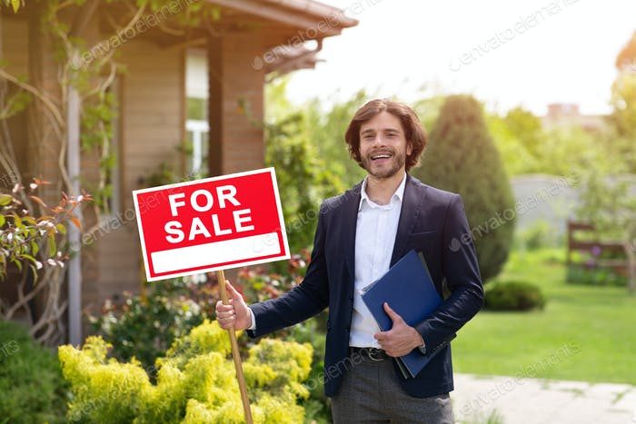Happy real estate agent holding FOR SALE sign near residential building outdoors