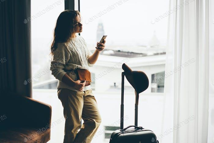 Frauen bleiben mit Koffer am Fenster und schreiben eine Nachricht in einem Hotelzimmer.