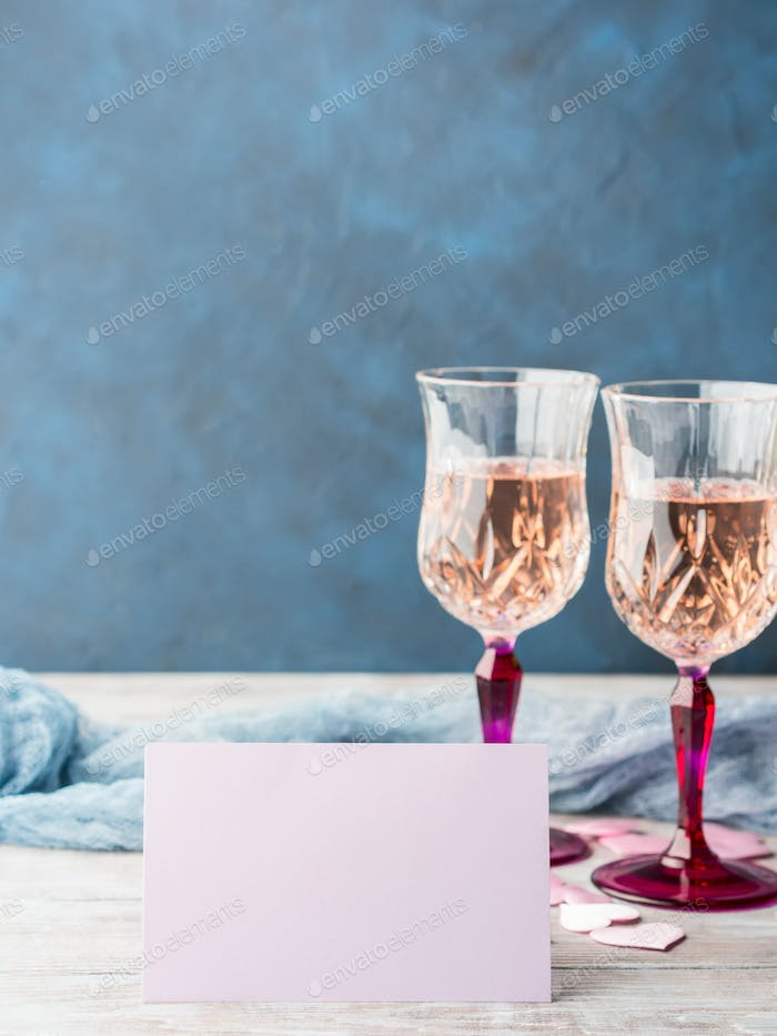 Two pink champagne glasses with blank paper card