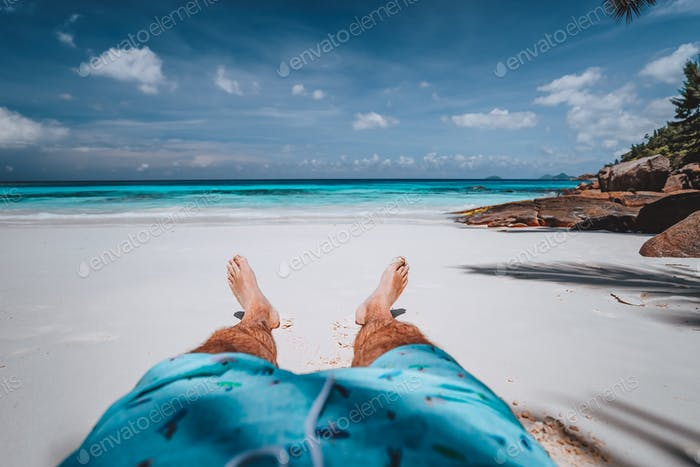 POV of male wearing swimming shorts with tanned legs on paradise white sand tropical exotic beach