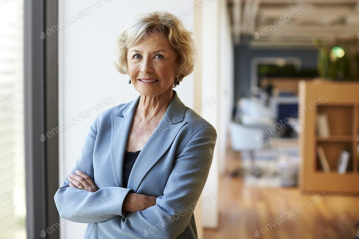 Portrait Of Smiling Senior Businesswoman In Modern Office Standing By Window