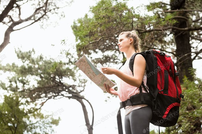 Blonde hiker with map searching for path in the nature