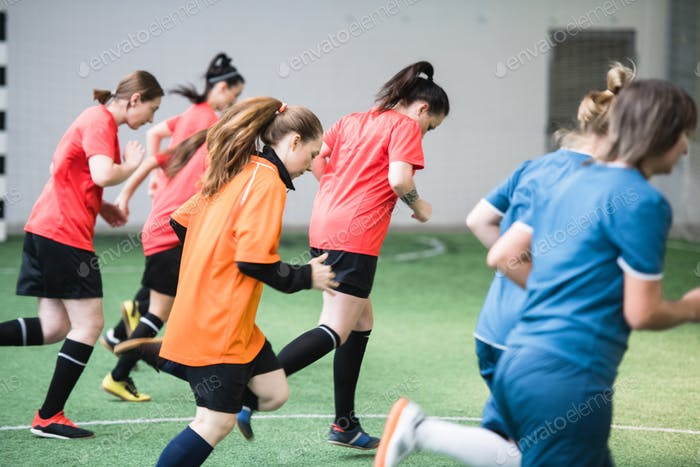 Group of active female footballers in sports uniform running down the field