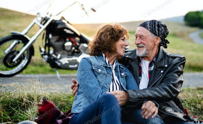 A senior couple travellers in love with motorbike in countryside.