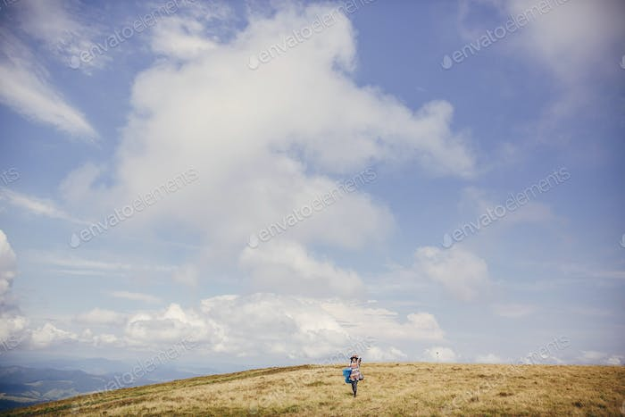 traveler hipster girl in hat with backpack exploring misty sunny mountains in clouds